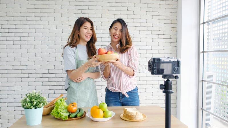 Dos bloggers asi?ticos jovenes de la comida de las mujeres que hablan mientras que registra el v?deo con el momento, el concepto  fotos de archivo