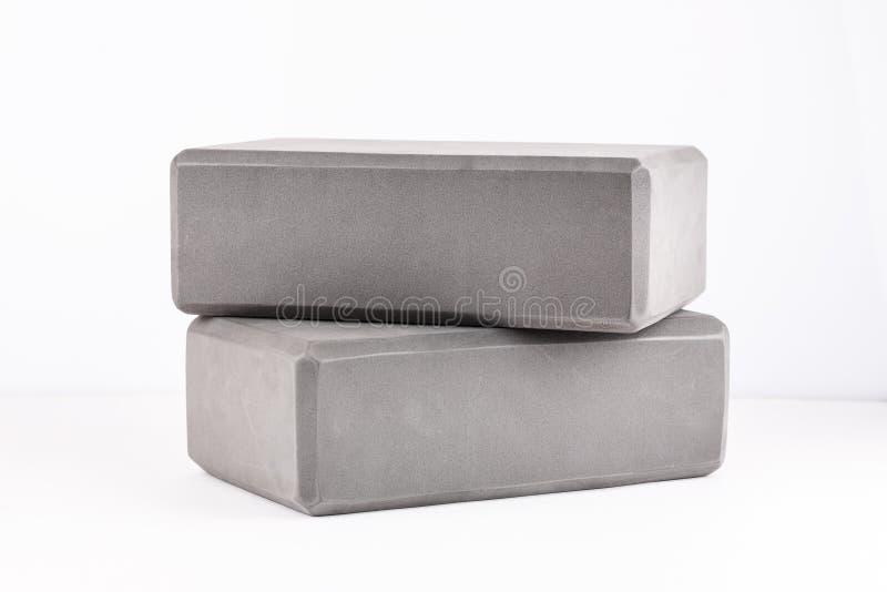 Dos bloques grises para la yoga en un blanco fotografía de archivo libre de regalías