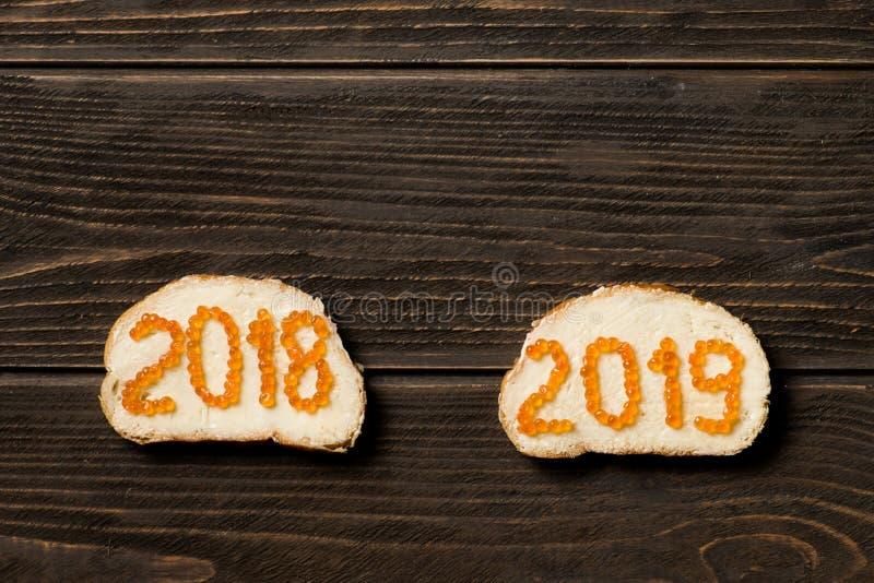 Dos bocadillos con mantequilla un caviar rojo en la forma de 2018 y de 2019 fotos de archivo