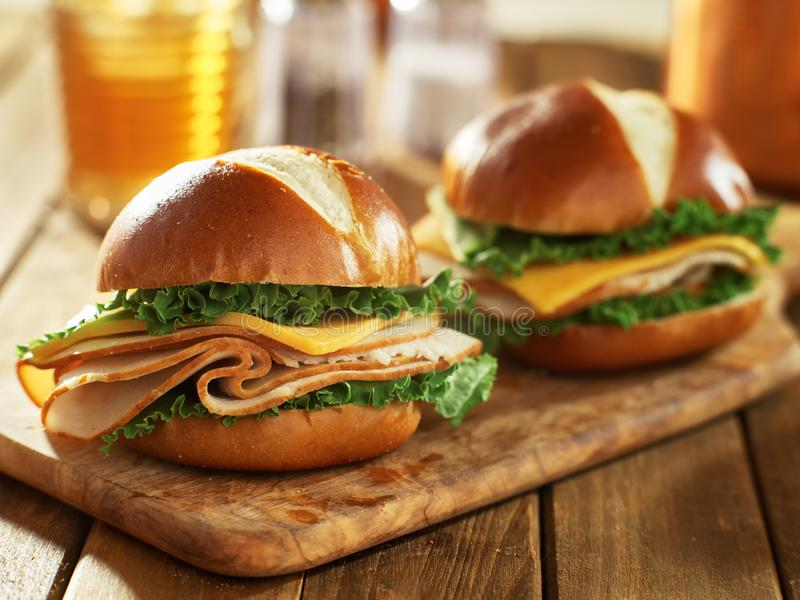 Dos bocadillos del pavo cortado frío y del queso del estilo en los bollos del pretzel foto de archivo libre de regalías