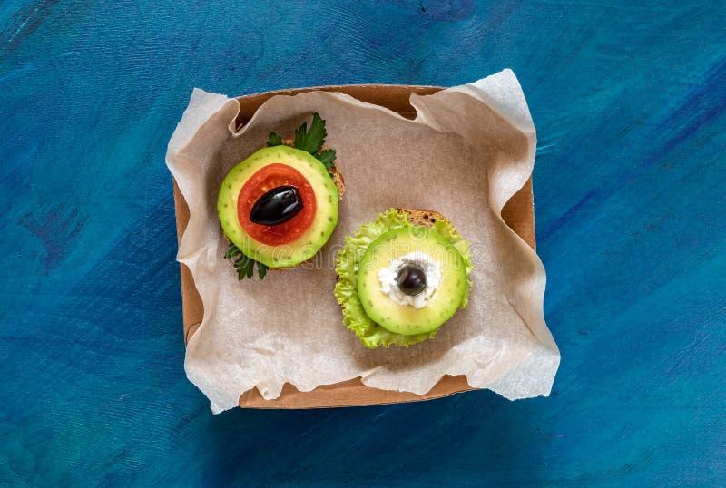 Dos bocadillos vegetarianos en pequeña caja de embalaje en fondo azul foto de archivo