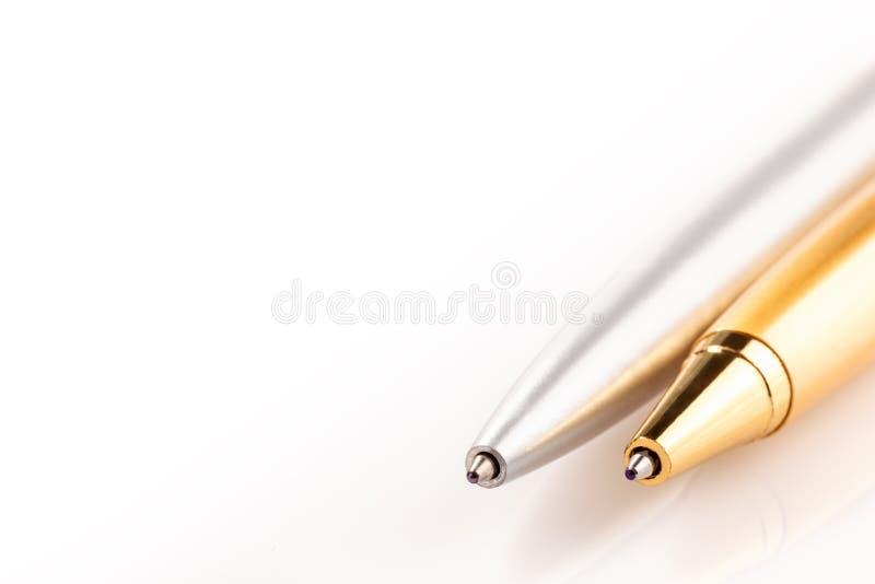 Dos bolígrafos hechos de la plata y del oro de acero Objetos en un fondo blanco imagen de archivo libre de regalías