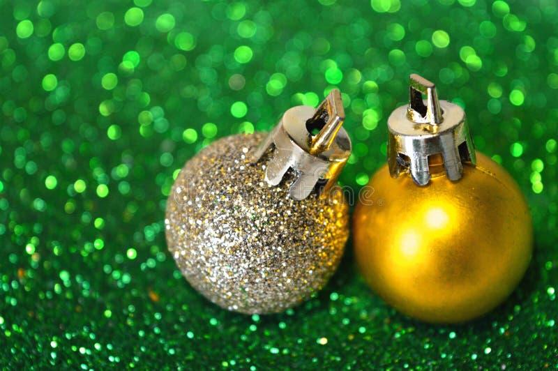 Dos bolas de oro de la Navidad en fondo borroso del brillo verde foto de archivo