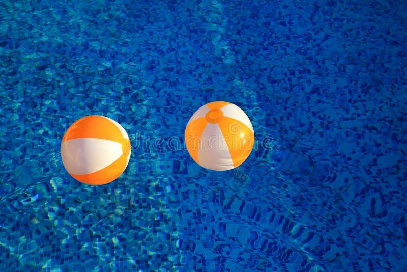 Dos bolas inflables blancas amarillas y juguete del aire de goma para la piscina en agua azul transparente Pelotas de playa que f imagen de archivo