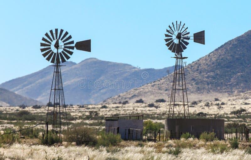 Dos bombas de agua del molino de viento en el calor haze en granja imágenes de archivo libres de regalías