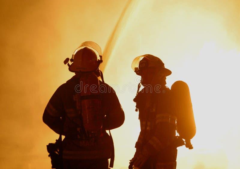 Dos bomberos en el fuego que rabia foto de archivo