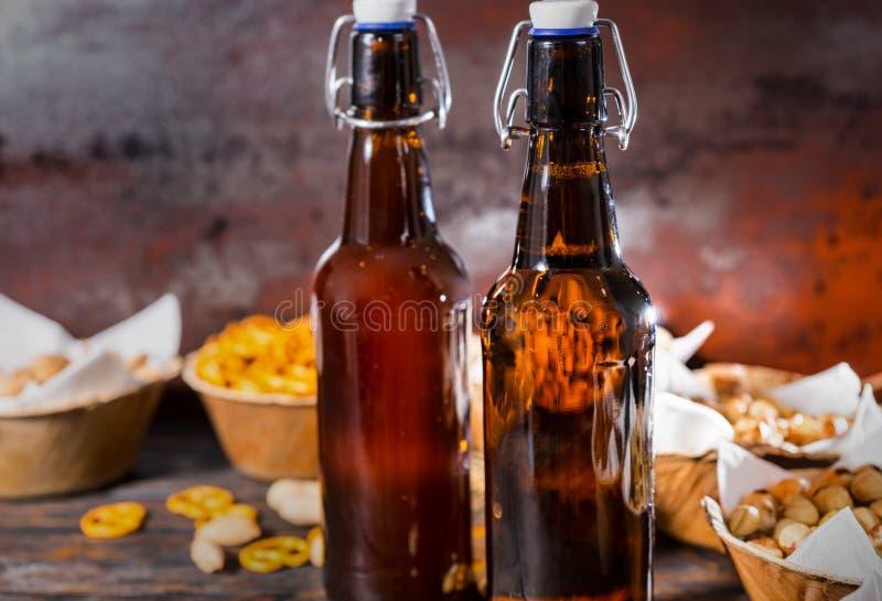 Dos botellas de cerveza, placas con los pistachos, pequeños pretzeles y guisante fotografía de archivo libre de regalías