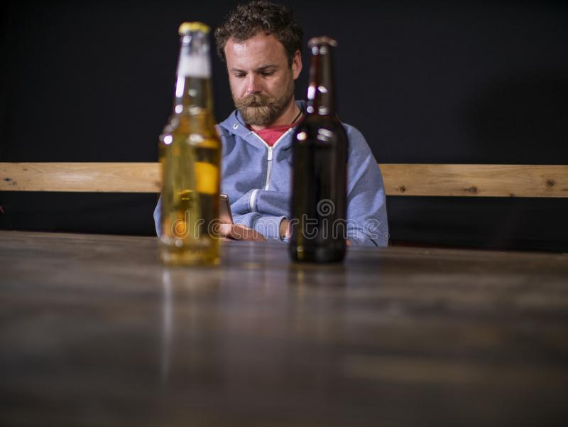 Dos botellas de cerveza se están colocando en la tabla contra la perspectiva de un hombre que se sienta que mire en el teléfono fotografía de archivo