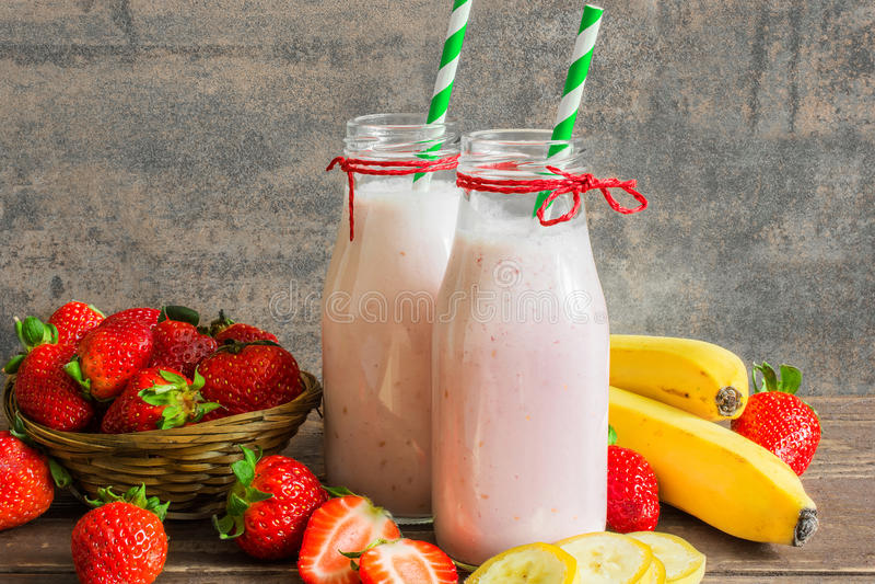 Dos botellas de smoothie de la fresa y del plátano imagen de archivo
