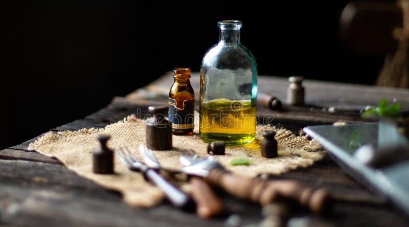 Dos botellas del vintage con aceite en harpillera con los viejos pesos, bifurcaciones en la tabla de madera rústica foto de archivo