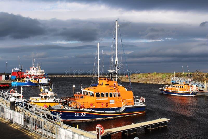 Dos botes salvavidas y otros buques en el puerto de Girvan foto de archivo libre de regalías