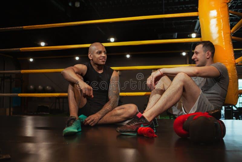 Dos boxeadores de sexo masculino que se resuelven junto en el gimnasio del boxeo fotos de archivo