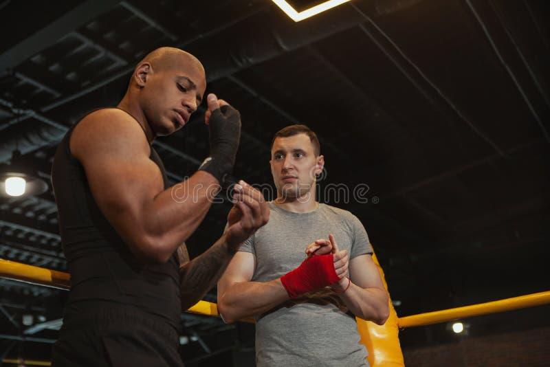 Dos boxeadores de sexo masculino que se resuelven junto en el gimnasio del boxeo foto de archivo libre de regalías
