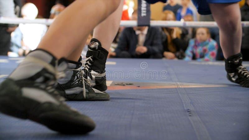 Dos boxeadores luchan en el ring de boxeo en shoeses del boxeo Sección baja del boxeador de sexo masculino que defiende contra ár fotos de archivo libres de regalías