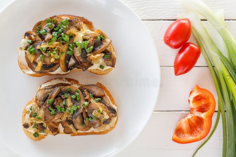 Dos bruschettes frescos con las setas en mentira en una placa al lado de los tomates, de las pimientas y de las cebollas en un fo imagen de archivo libre de regalías