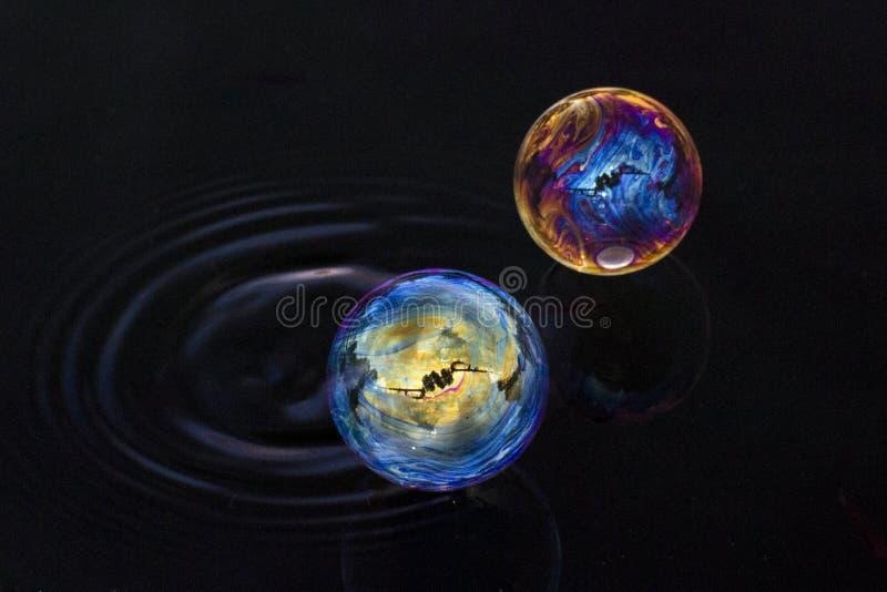 Dos burbujas de diversos colores que flotan sobre el agua ilustración del vector