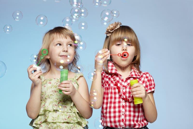 Dos burbujas de jabón de la niña que soplan foto de archivo libre de regalías