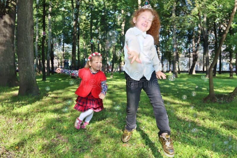 Dos burbujas de jabón felices de la captura de las niñas entre árboles fotos de archivo