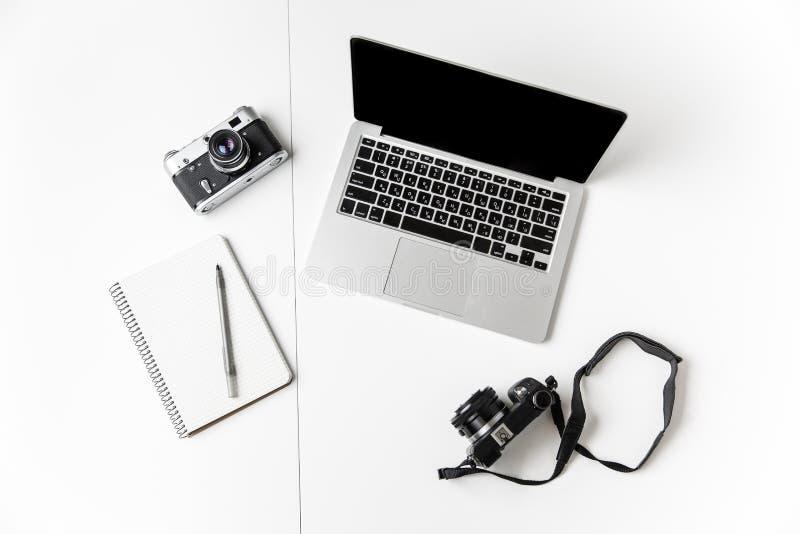 Dos cámaras, libreta con la pluma y ordenador portátil de la pantalla en blanco imagen de archivo