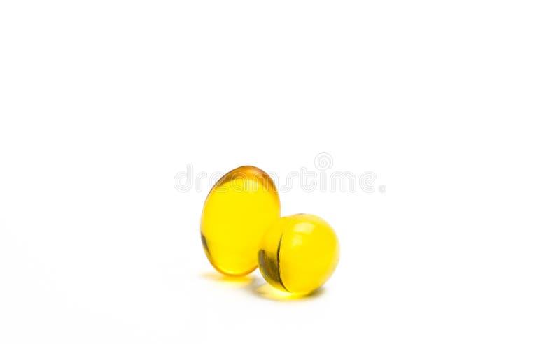 Dos cápsulas de aceite de hígado de bacalao aislado en el fondo blanco La fuente de Omega-3 y vitamina A y D ayuda al desarrollo  imagen de archivo libre de regalías