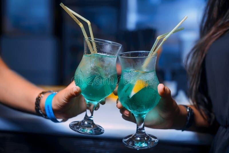 Dos cócteles del alcohol que mantienen manos de las muchachas en el club de noche fotos de archivo libres de regalías