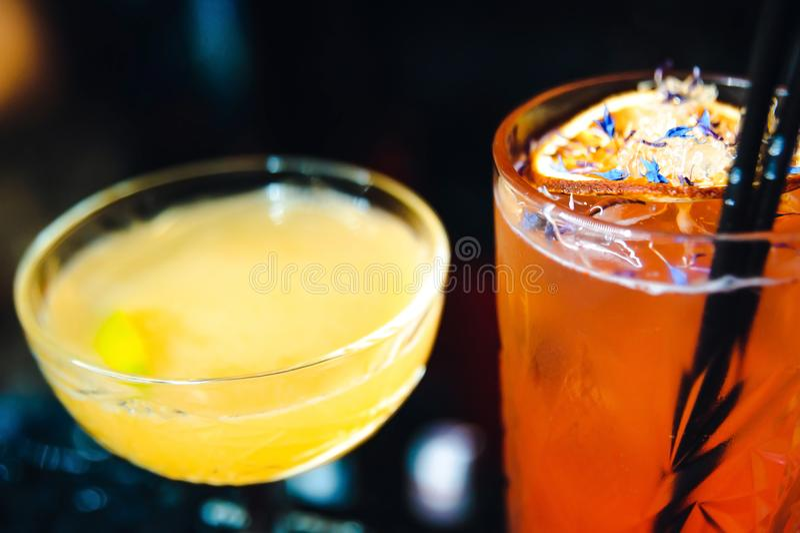 Dos cócteles en el contador de la barra bebidas del rojo anaranjado y del amarillo foto de archivo