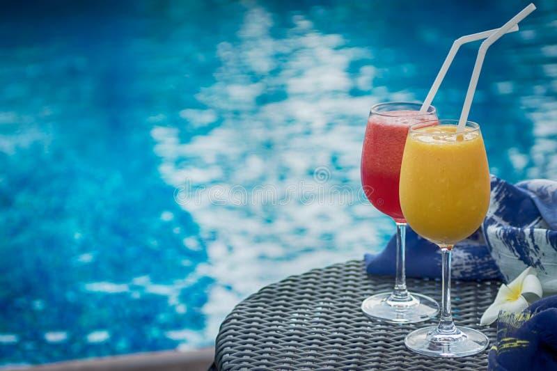 Dos cócteles rojos y amarillos en la tabla contra piscina imagenes de archivo