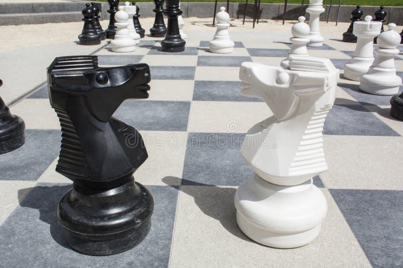 Dos caballeros en el tablero de ajedrez de la calle con las piezas de ajedrez imagen de archivo