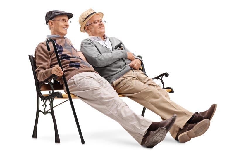 Dos caballeros mayores que se sientan en un banco fotos de archivo