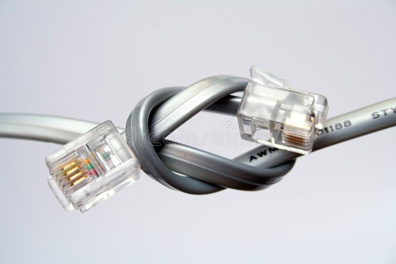 Dos cables de teléfono con las extremidades anudadas fotografía de archivo libre de regalías