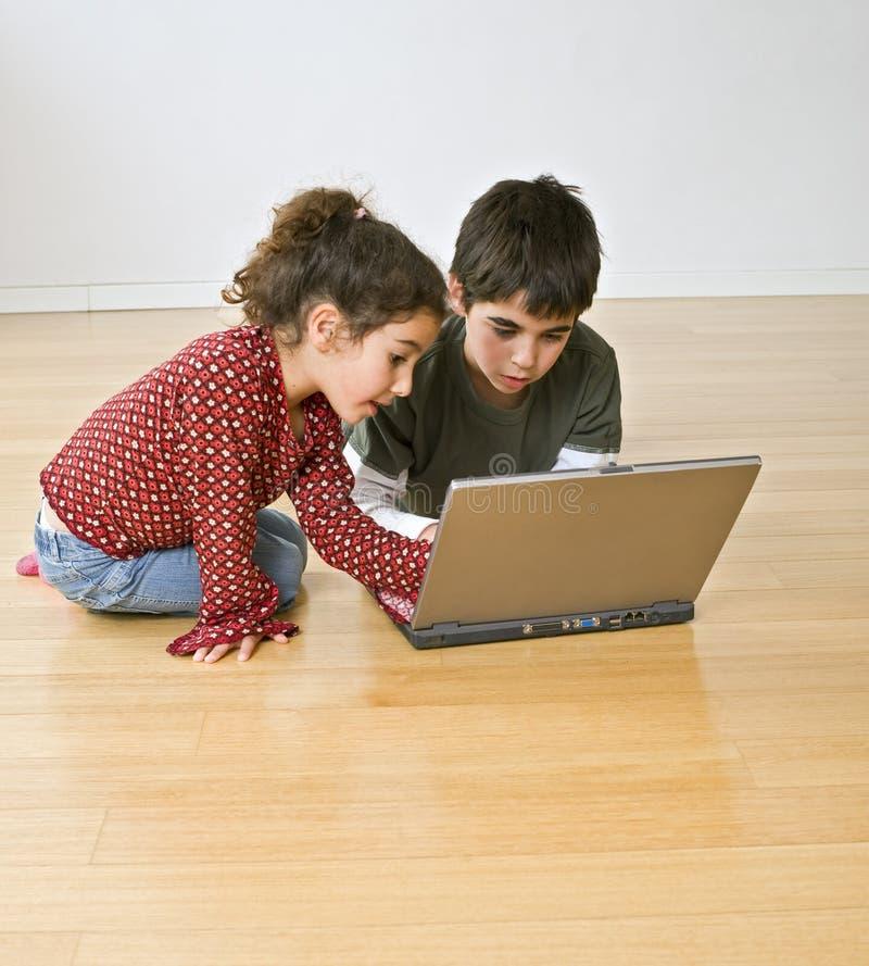 Dos cabritos con el ordenador portátil fotografía de archivo libre de regalías