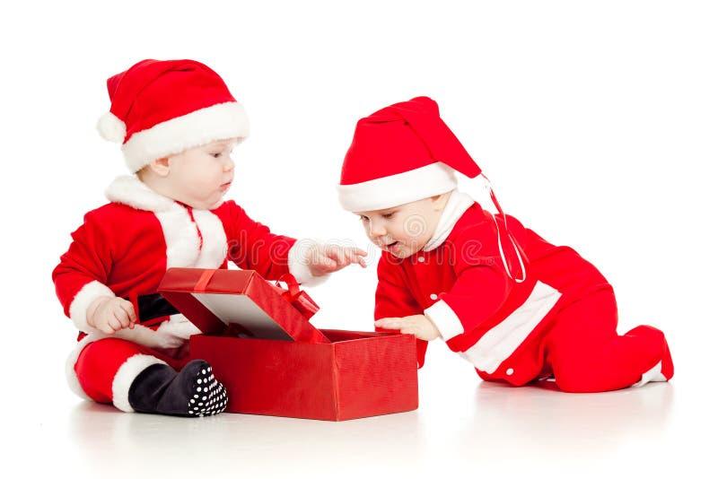 Dos cabritos divertidos en Santa arropan con el rectángulo de regalo fotografía de archivo libre de regalías