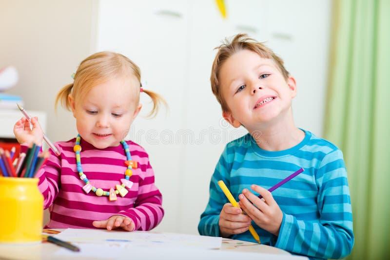Dos cabritos que drenan con los lápices del colorante foto de archivo