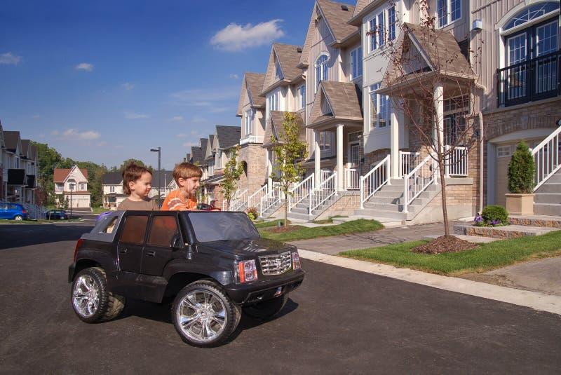 Dos cabritos que se divierten en el coche del juguete imágenes de archivo libres de regalías