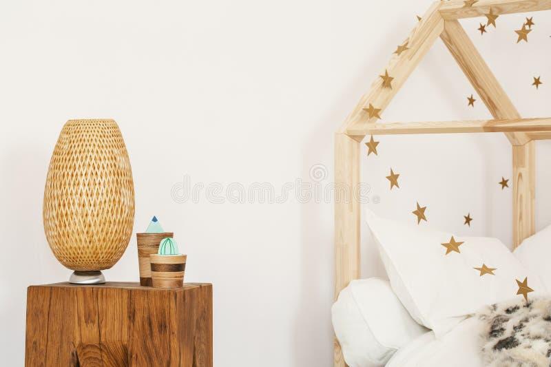 Dos cactus artificiales y lámpara de mimbre que se colocan en bedsi de madera fotografía de archivo