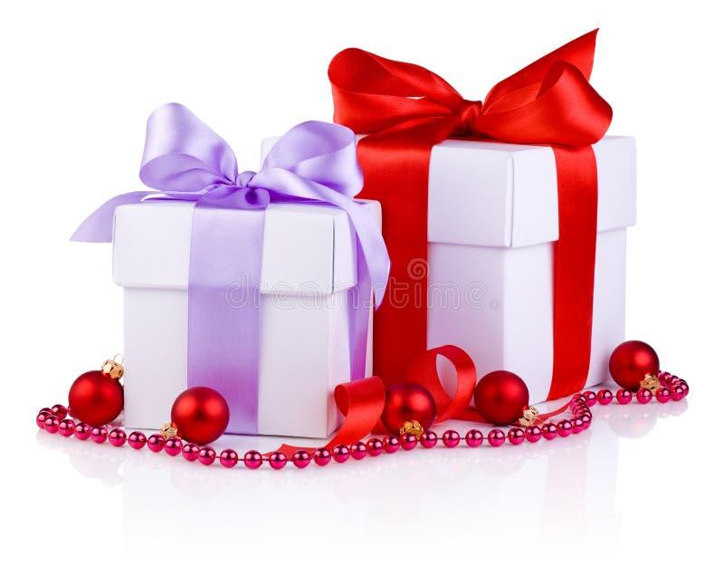 Dos cajas blancas atadas con una cinta de satén arquean, las bolas rojas de la Navidad imágenes de archivo libres de regalías