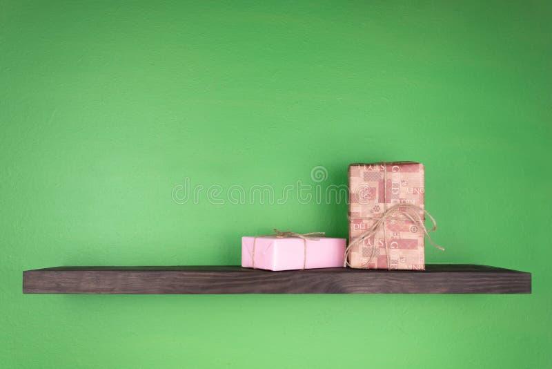 Dos cajas de regalo en un estante del color oscuro con la textura de madera montada en una pared verde imagenes de archivo