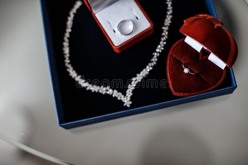Dos cajas rojas del anillo con anillos en ellos y un collar cerca de ellos están mintiendo dentro del joyero azul fotografía de archivo
