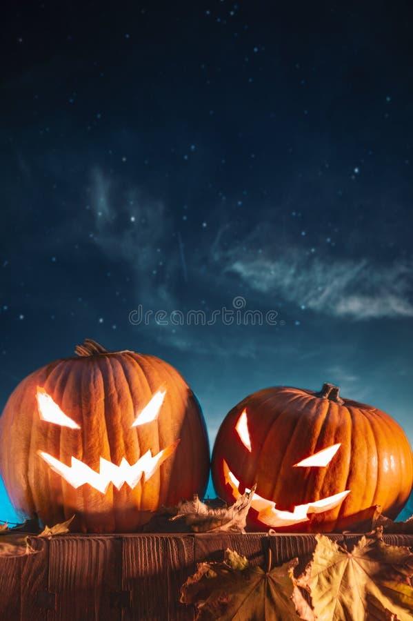 Dos calabazas de Halloween en la cerca con el cielo estrellado fotos de archivo libres de regalías