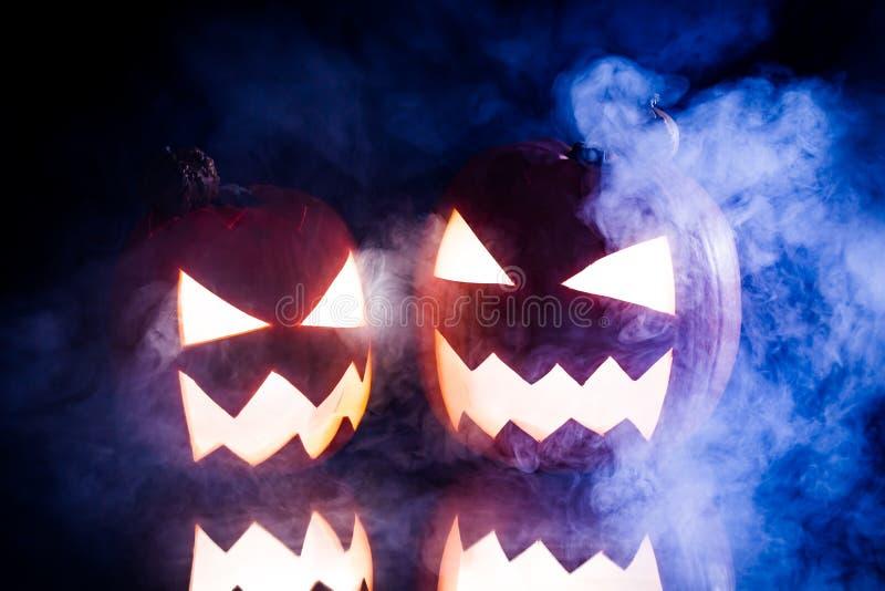 Dos calabazas que fuman para Halloween y la luz azul foto de archivo