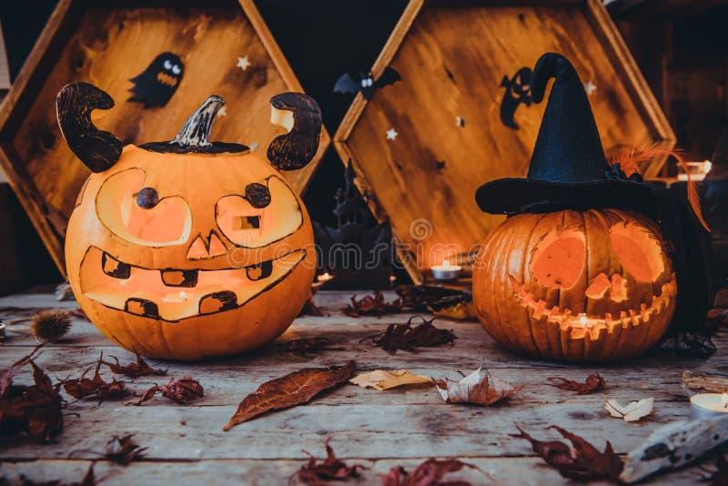 Dos calabazas talladas y otros símbolos de Halloween en fondo de madera Linterna del enchufe de la cabeza de la calabaza de Hallo foto de archivo libre de regalías