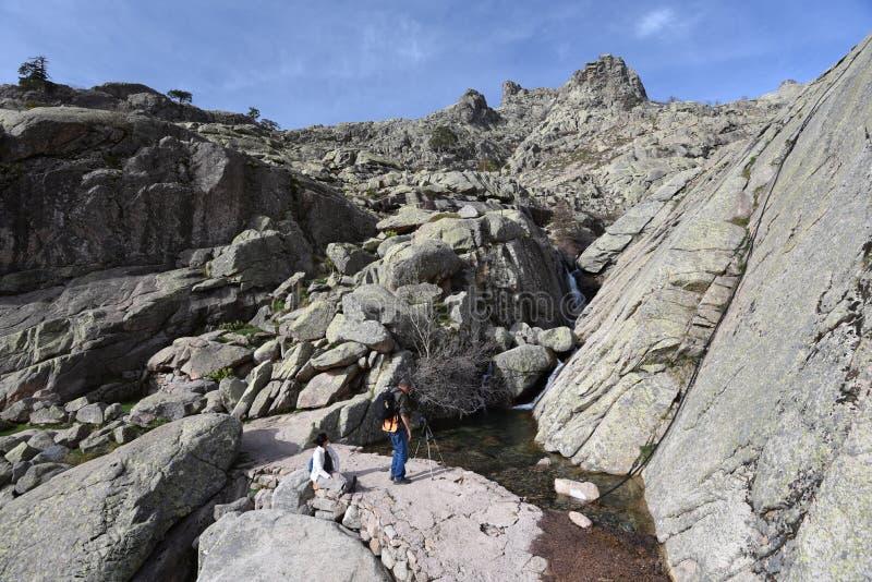 Dos caminantes cerca de la corriente de la montaña imagen de archivo libre de regalías