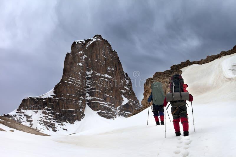 Dos caminantes en montañas y cielo nevosos de la tormenta imagenes de archivo