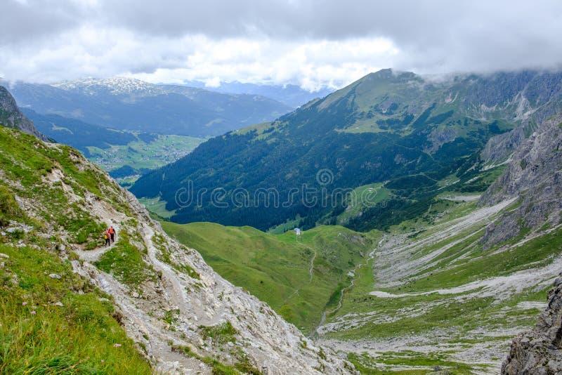 Dos caminantes que descienden en un valle en los moutains de Allgaeu, Austria fotografía de archivo
