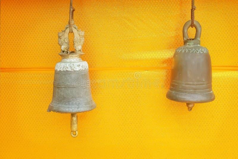 Dos campanas de cobre amarillo antiguas que cuelgan en fondo de la tela del oro en el templo en Tailandia imagenes de archivo
