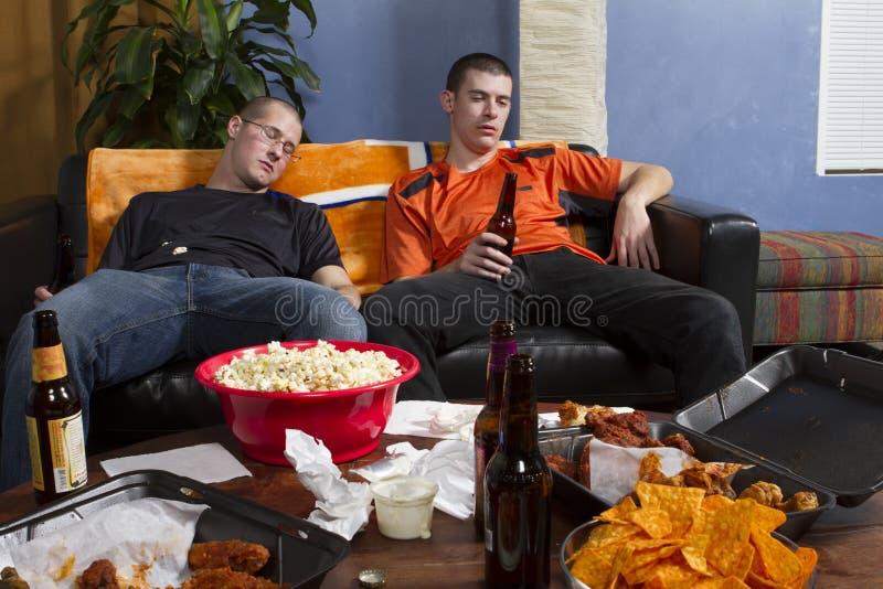 Dos cansaron a hombres después de mirar el juego de los deportes en la TV, horizontal fotos de archivo libres de regalías