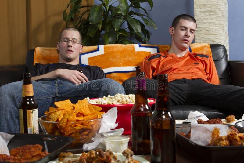 Dos cansaron a hombres después de mirar el juego de los deportes en la TV, horizontal fotos de archivo