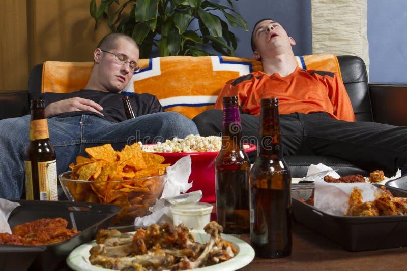 Dos cansaron a hombres después de mirar el juego de los deportes en la TV, horizontal imagenes de archivo
