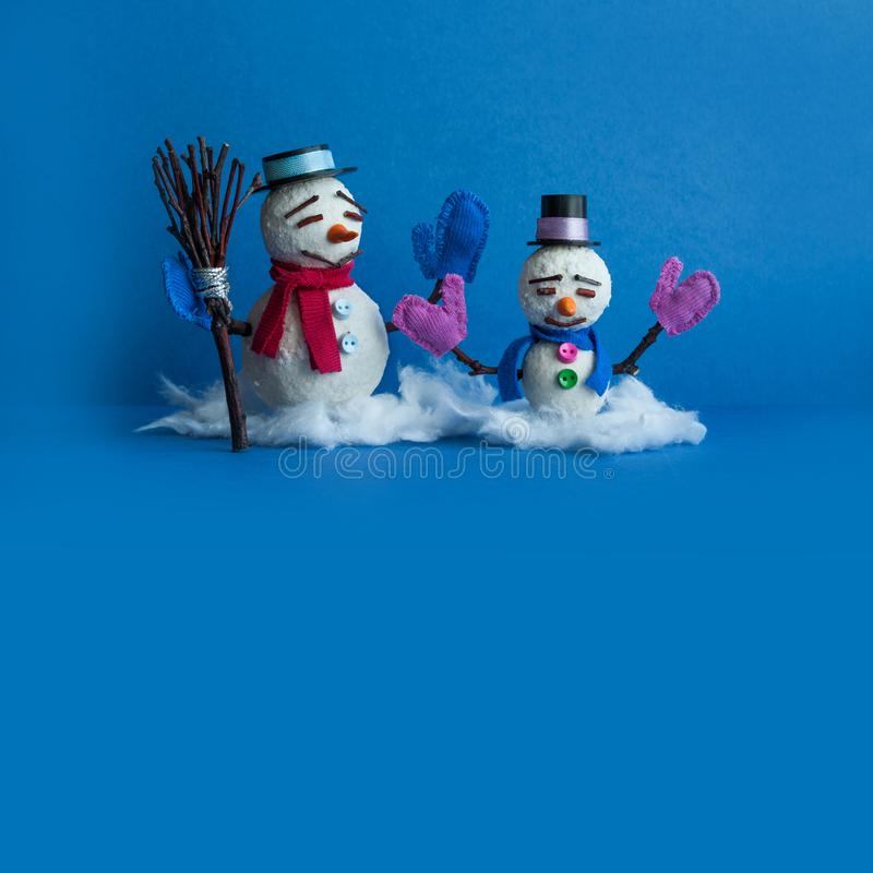 Dos caracteres de los muñecos de nieve en fondo azul Tarjeta de felicitación cómica del Año Nuevo de Navidad con el muñeco de nie fotos de archivo libres de regalías