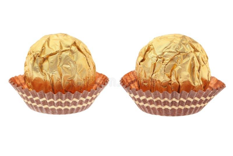 Dos caramelos de chocolate envueltos en oro. imagen de archivo